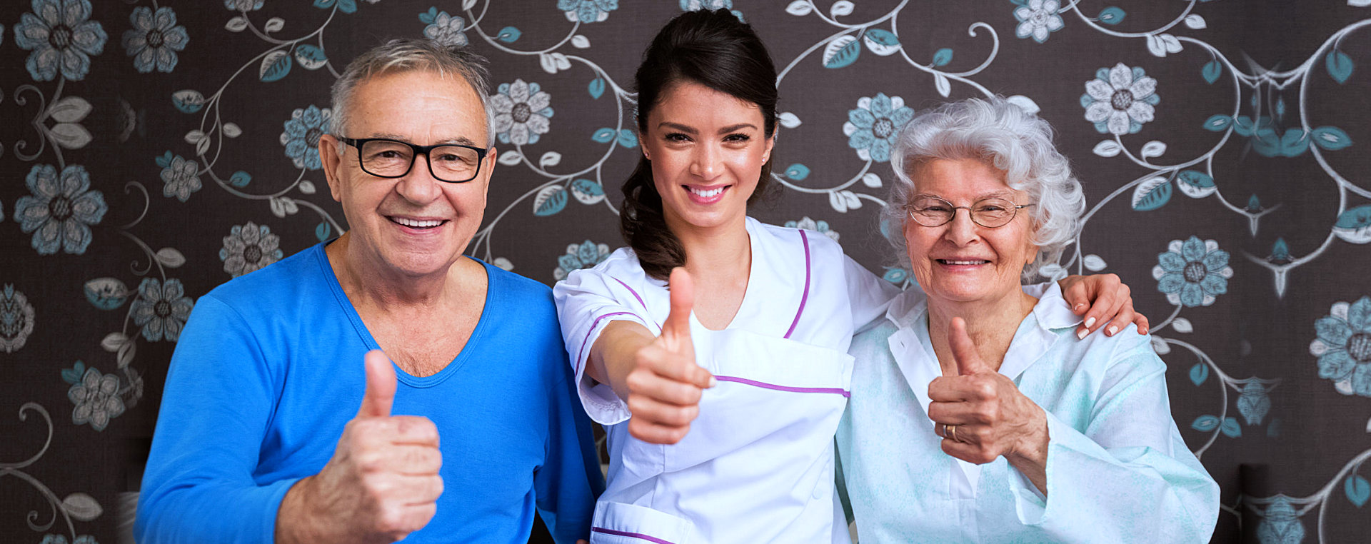 elderly couple and a caregiver doing thumb's up