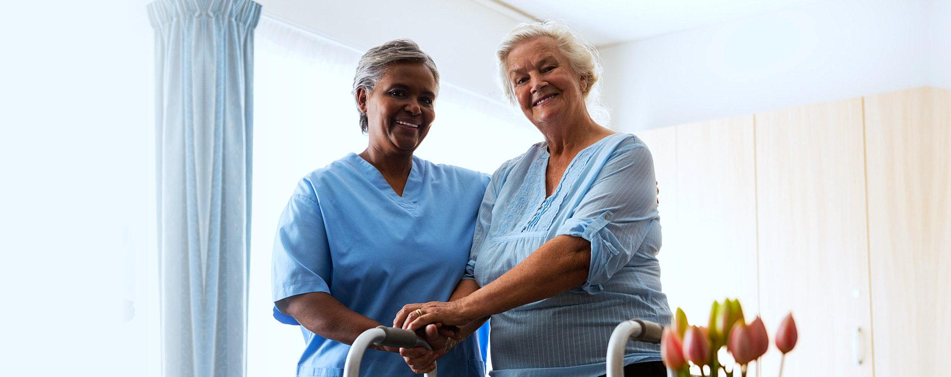 elder woman and her caregiver smiling